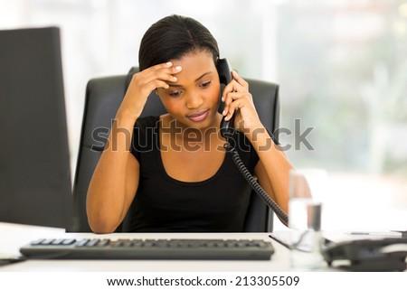 tired black businesswoman using landline phone in office - stock photo