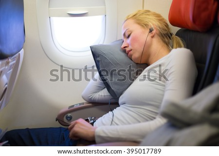 Tired blonde casual caucasian lady listens to music while napping on uncomfortable seat while traveling by airplane. Commercial transportation by planes. - stock photo