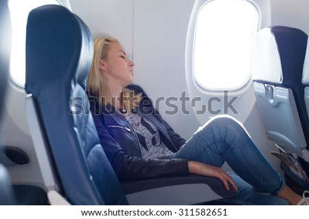 Tired blonde casual caucasian lady napping on uncomfortable seat while traveling by airplane. Commercial transportation by planes. - stock photo