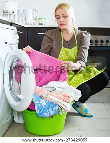 Tired blonde girl doing laundry with washing machine at home kitchen - stock photo