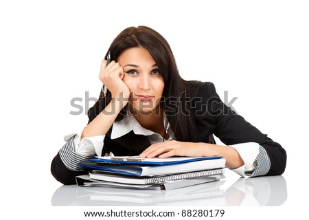 tired bored overworked business woman sitting at the desk with folder stack, looking sad at camera. Isolated on white background.