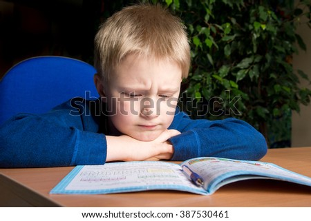 Tired boring boy don't want to do his difficult school homework - stock photo