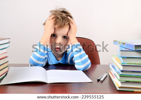 tired boy sitting at a desk and holding hands to head horizontal - stock photo