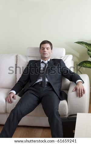 Tired business man on sofa - stock photo