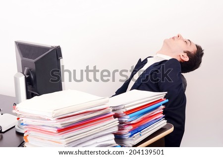 Tired business man sleeping at work. Exhausted worker sleeping at the desk.