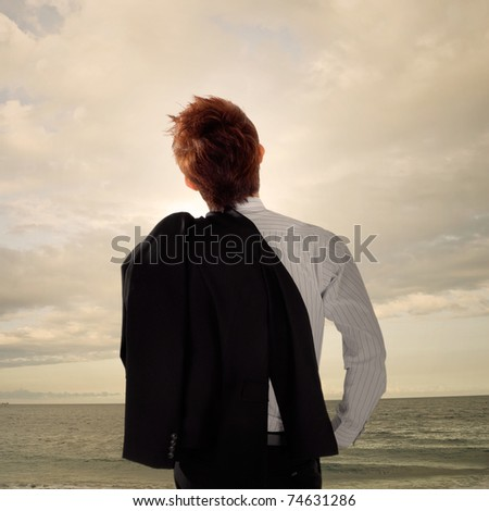 Tired business man standing in outdoor and looking far away of ocean. - stock photo