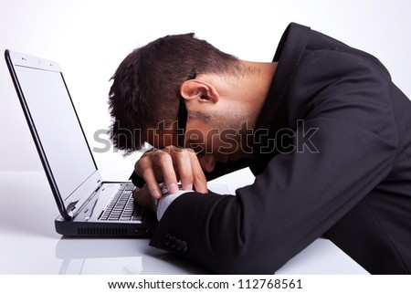 Tired business man with head and hands down on laptop - stock photo