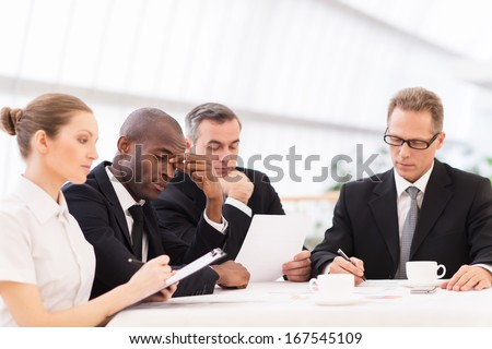 Tired business people. Four business people in formalwear looking tired while sitting together at the table - stock photo