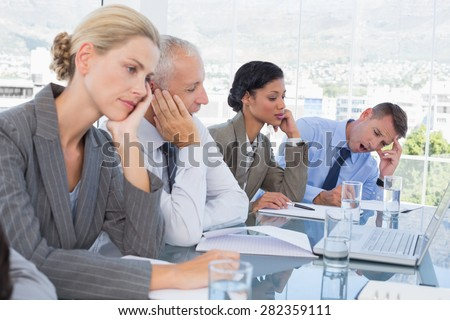 Tired business team at conference in the office - stock photo