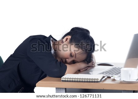 Tired business woman sleeping at her desk. Isolated on white background. Model is Asian woman.