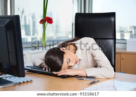 Tired business woman sleeping on the keyboard in office - stock photo