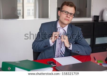 Tired businessman adjusting his tie. - stock photo