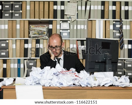 Tired Businessman at a messy office - stock photo