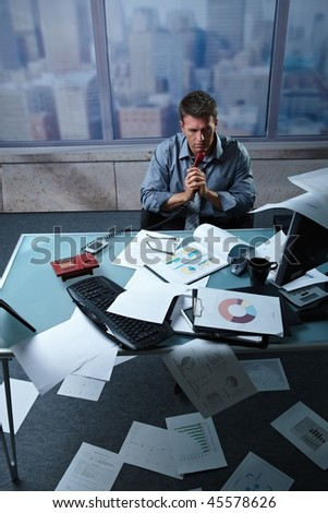 Tired businessman calling from office papers lying all around, picture taken from high angle. - stock photo