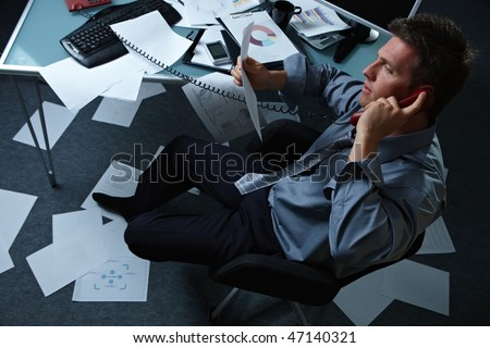 Tired businessman calling from office with shoes off papers lying all around, picture taken from high angle. - stock photo