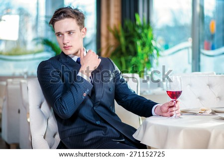 Tired businessman from work. Confident businessman in formal wear sitting at a table in a restaurant while holding a glass of wine and looking at the camera - stock photo