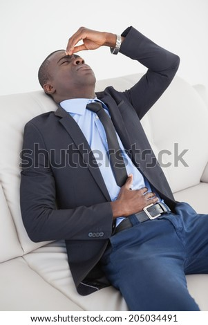 Tired businessman getting headache on the sofa at home in the living room - stock photo