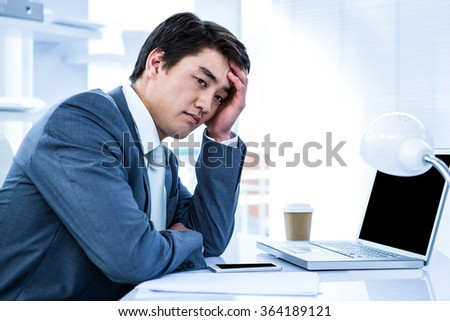 Tired businessman holding his head in his office - stock photo