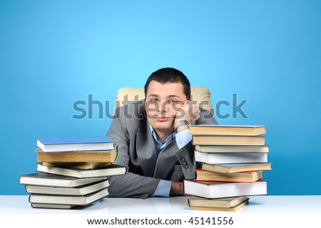 Tired businessman in the books on blue background