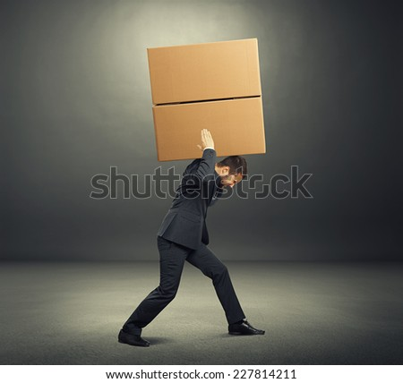 tired businessman in the suit carrying two heavy boxes. photo in the dark room - stock photo
