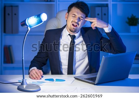 Tired businessman is working with laptop and holding fingers to his temple - stock photo