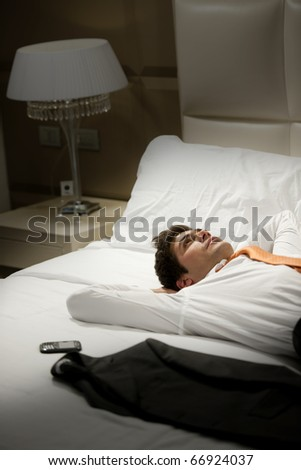 Tired Businessman resting in hotel room - stock photo