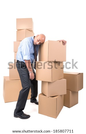 Tired businessman resting over a stack of cardboard boxes