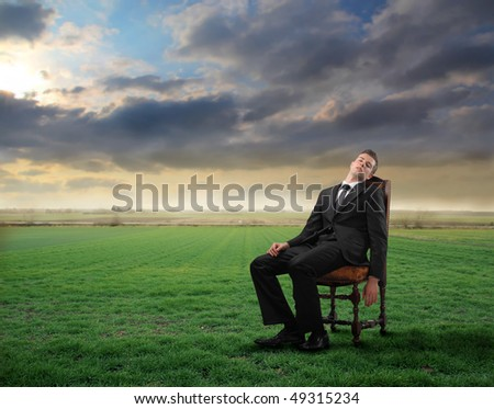 Tired businessman sitting on a chair on a green meadow - stock photo