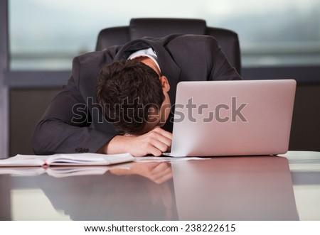 Tired businessman sleeping on a laptop - stock photo