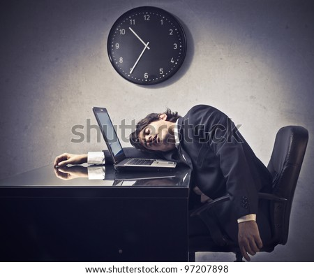 Tired businessman sleeping on a laptop with clock in the background - stock photo