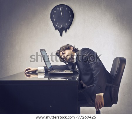 Tired businessman sleeping on his laptop with clock in the background - stock photo