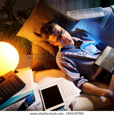 Tired businessman sleeping on sofa at home surrounded by paperwork. - stock photo