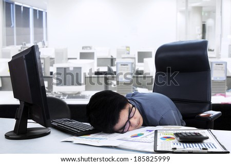 Tired businessman sleeping on the desk. shoot at office - stock photo