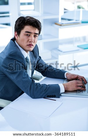 Tired businessman using his computer in his office - stock photo