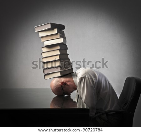 Tired businessman with his head on a table and a stack of books on it - stock photo