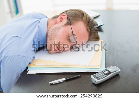 Tired businessman with stack of files on desk in his office - stock photo