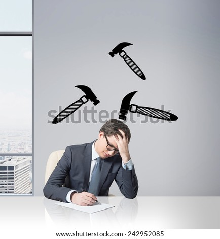 tired businessman working in office with hammer over head