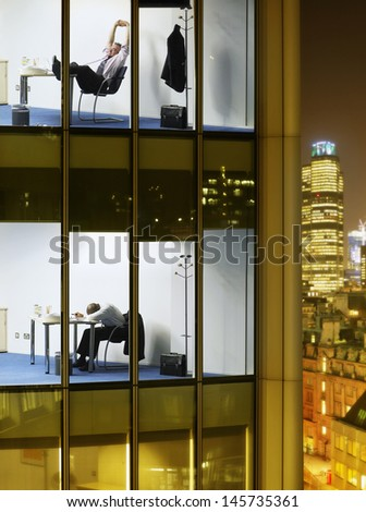 Tired businessmen working late night in different office blocks - stock photo