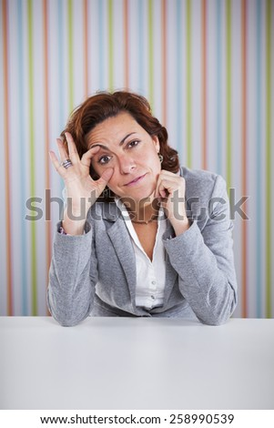 Tired businesswoman at the office - stock photo