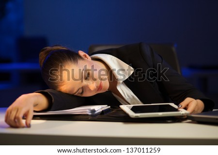 Tired businesswoman falling asleep in the office late at night - stock photo
