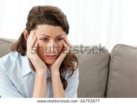 Tired businesswoman having a headache on the sofa at home - stock photo