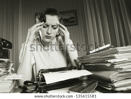 Tired businesswoman is sitting at a table full of paperwork - stock photo