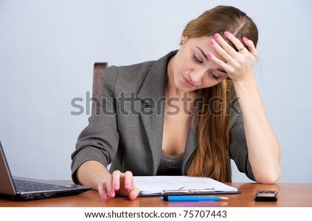 Tired businesswoman reading document at the office - stock photo