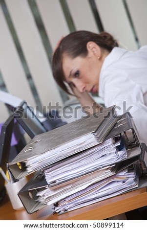 tired businesswoman sitting at her desk with lots of folders - focus on documents in foreground - stock photo