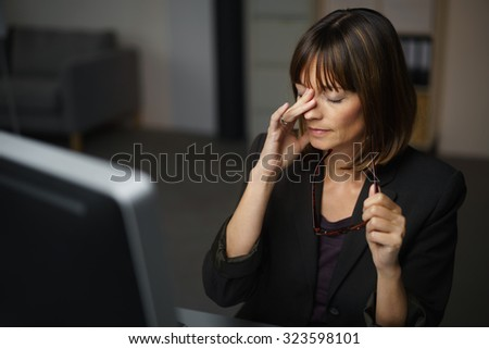 Tired Businesswoman Sitting at her Table, Takes Off her Eyeglasses and Rubs her Eyes - stock photo