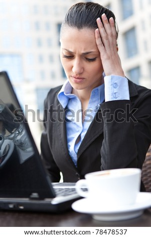 tired businesswoman sitting in front of her laptop, and holding hand on her head - stock photo
