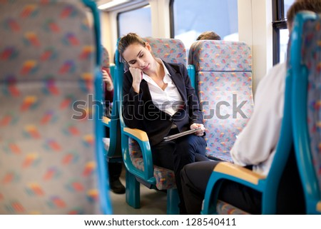 Tired businesswoman sleeping on the train - stock photo