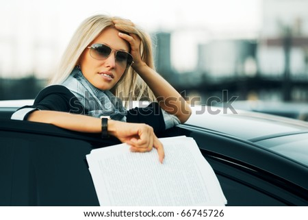 Tired businesswoman with financial reports. - stock photo