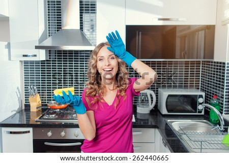 Tired but happy. Cheerful young woman with blue rubber gloves cleaning her kitchen. - stock photo