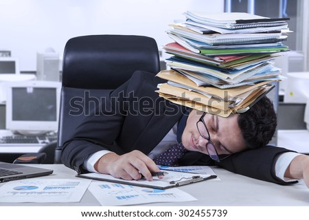 Tired caucasian businessman sleeping on the table with a stack of documents on his head - stock photo